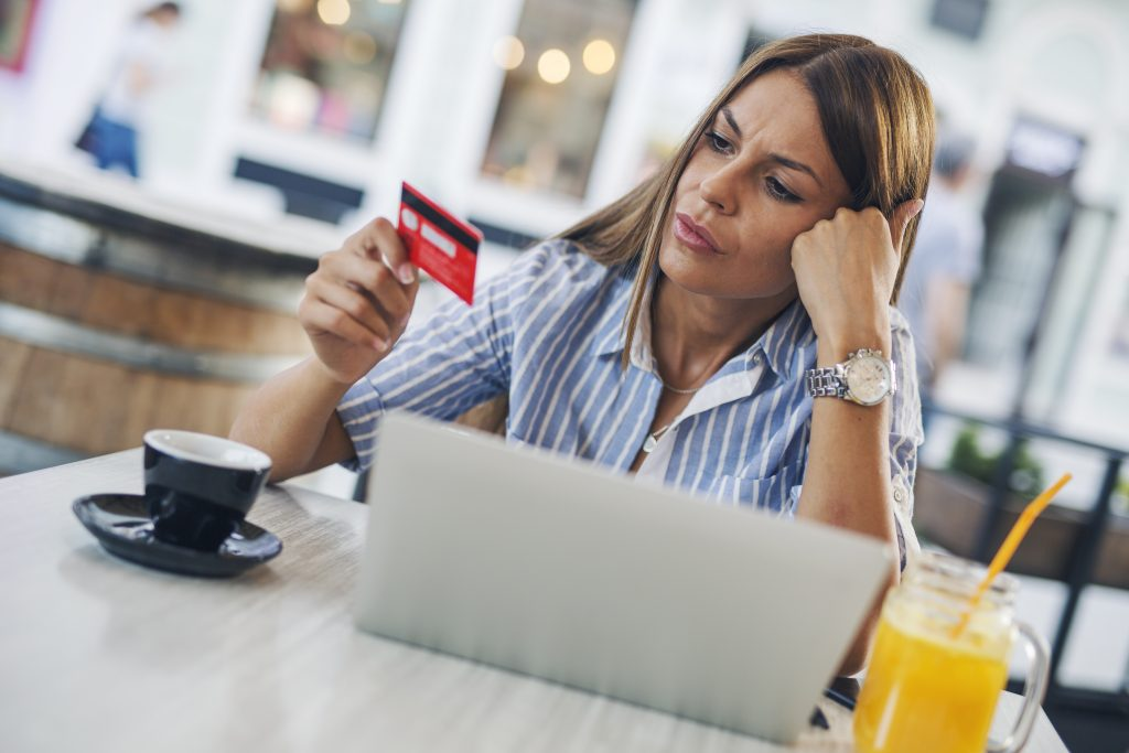 Woman in coffee shop looking at declined credit card